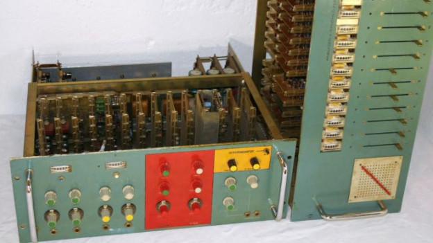 Gerät mit vielen Kabeln und Knöpfen - grüne Verschalung.