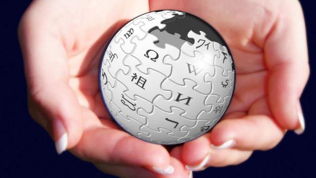 Zwei Hände halten eine Weltkugel, die aus Puzzleteilen besteht – das Logo von Wikipedia.