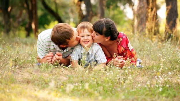 Eine Mutter und ein Vater liegen mit ihrem Kind auf der Wiese.