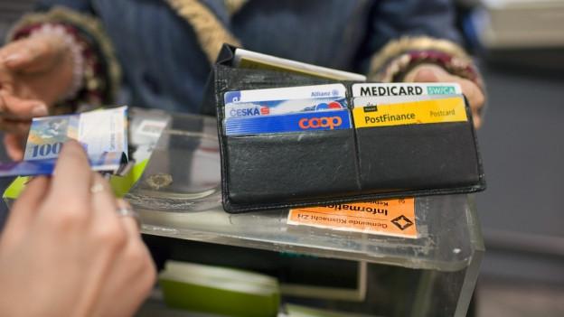 Ein Portemonnaie auf einer Theke, diverse Bankkarten.