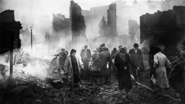 Eine Stadt in Trümmern, Menschen laufen durch Schutt und Asche.