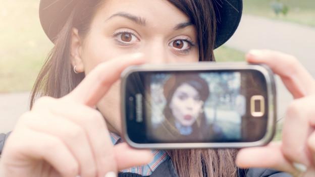 Frau macht ein Selfie mit dem Smartphone.