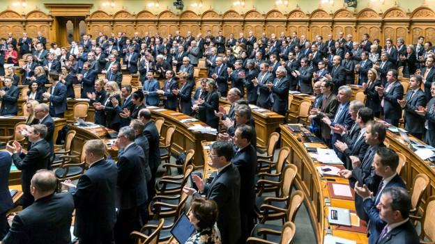 Saal des Parlamentes im Bundeshaus Bern. Die Parlamentarier stehen und aplaudieren.