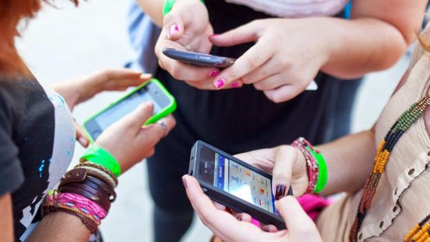 Drei Frauen schauen auf ihre Handys.