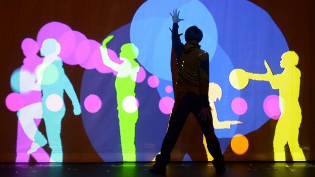 Eine Disco mit bunten Punkten ander Wand, davor tanzen Menschen.