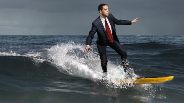 Ein Mann in Anzug reitet auf einem Surfbrett.