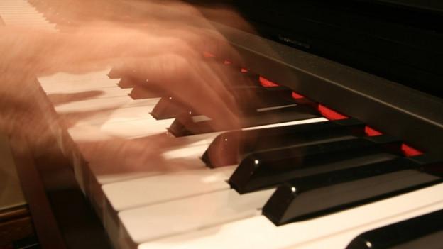 Finger fliegen über eine Klaviertastatur.