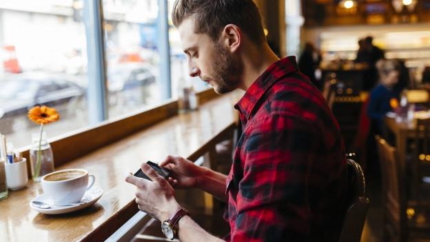 Mann sitzt in einem Cafe und schaut auf sein Smartphone.