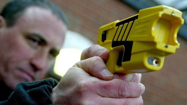 Man hält eine gelbe Elektroschock-Pistole.
