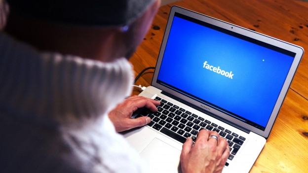 Ein Mann sitzt vor einem Laptop, auf dem Bildschirm steht «Facebook».