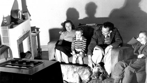 Eine Familie sitzt mit ihrem Hund vor dem Fernseher.