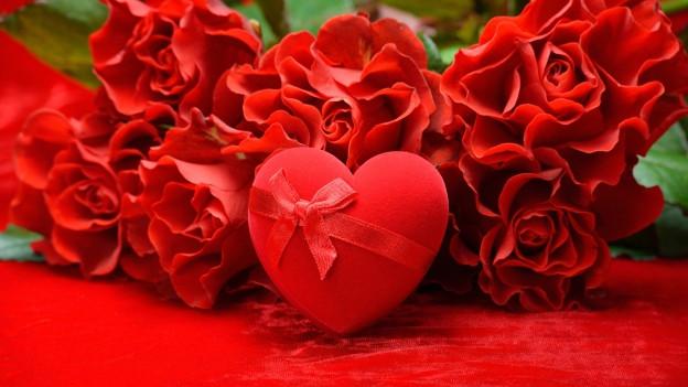Eine herzförmige Dose vor roten Rosen.