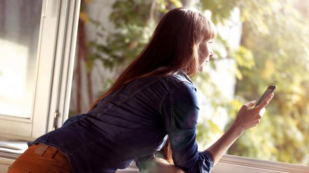 Eine Frau lehnt sich zum Fenster hinaus, in der Hand hat sie ein Handy.