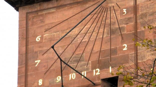 Auf der Wand des Basler Münsters ist ein Rechteck aufgemalt. Von der Ecke rechts oben zeigen Strahlen mit Zahlen auf alle Seiten.