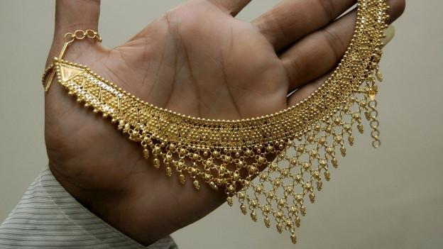 Eine Hand hält eine Kette aus Gold.
