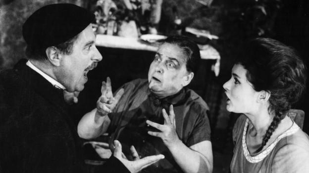 Filmstill: Ein Mann schreit, zwei Frauen schauen ihn entsetzt an.