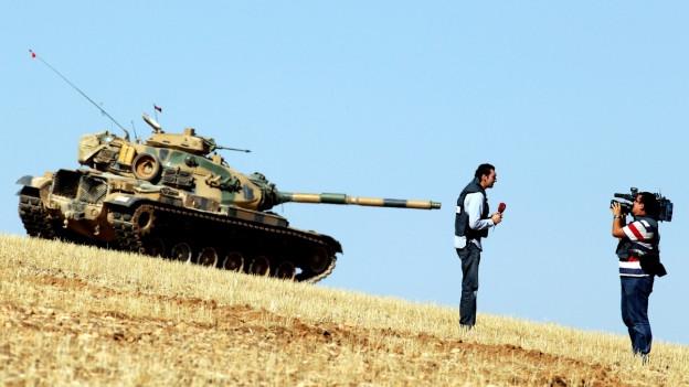 Ein Panzer, daneben ein Journalist mit Mikrofon; er wird von einem Kameramann gefilmt.