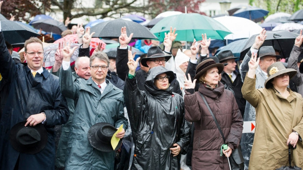 Menschen im Regen, und alle strecken sie die rechte Hand gen Himmel.