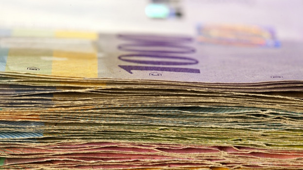 Ein Stapel mit Schweizer Geldscheinen. Oben liegt einer 1000-Franken-Note.