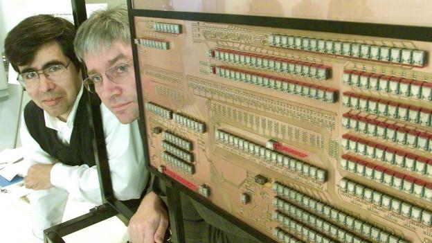 Ein reisiger Rechner mit der Aufschrift «Z3 Rechenwerk», zwei Männer schauen hervor.