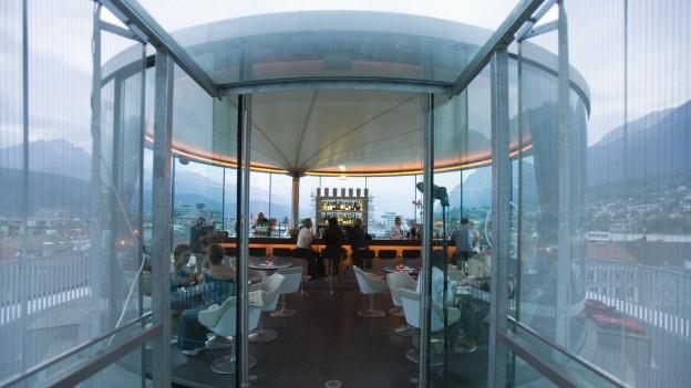 Eine Glaskuppel, darin ein Restaurant mit Bar und Sitzplätzen.