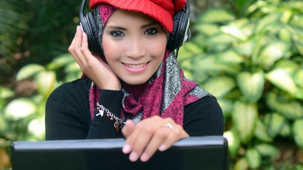 Junge asiatische Frau mit Kopftuch und Kopfhörern.