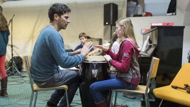 Ein Mädchen beim Trommeln mit dem Musiklehrer.