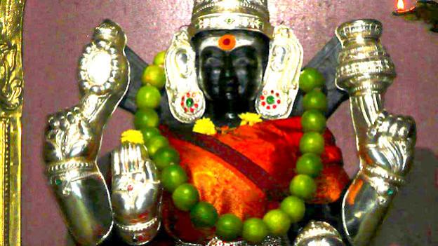 Statue einer Götterfigur mit schwarzen Gesicht.