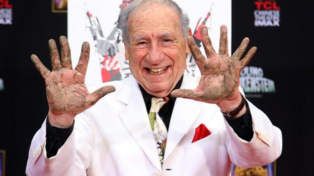 Mel Brooks streckt seine schmutzigen Hände vor sich aus.