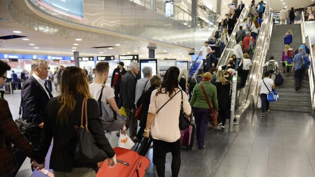 Flugreisende in der Ferienzeit stauen sich an der Rolltreppe