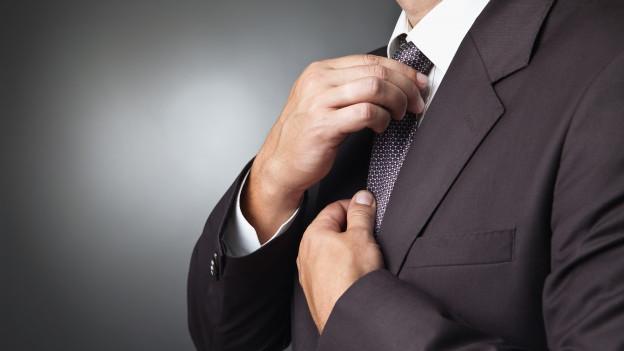 Ein Mann bindet sich die Krawatte.