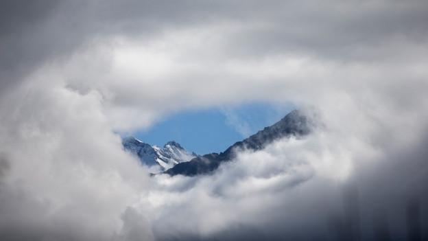 Eine Wolkendecke hat ein Loch und zeigt dahinter die Alpen.
