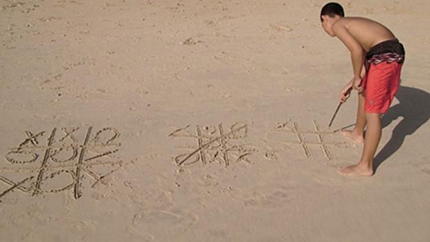 Ein Junge spielt an einem Strand Tic Tac Toe.