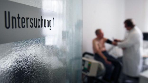 Blick durch einen Türspalt: Ein Arzt untersucht einen Patienten