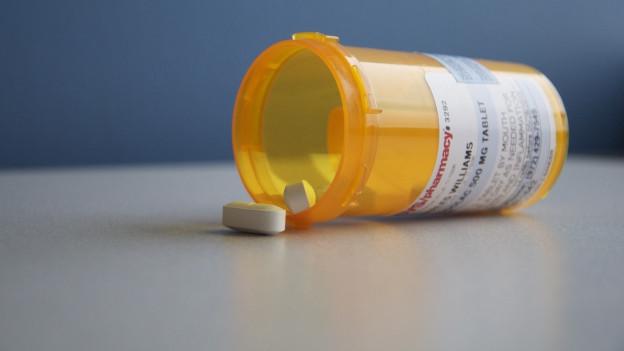 Eine weisse Pille vor einer gelben Pillendose, die auf dem Tisch liegt.