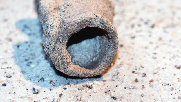 Ein Fulgurit: Eine unebene steinerne Röhre.