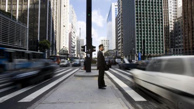 Ein Mann steht auf einer Verkehrsinsel in dichtem Verkehr.