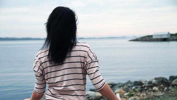 Frau blickt hinaus aufs Meer.