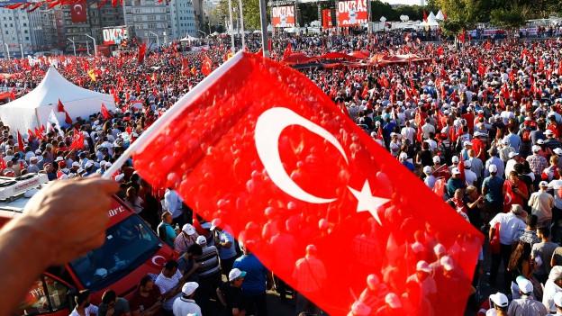 Hand schwenkt türkische Fahne über einer Menschenmenge.