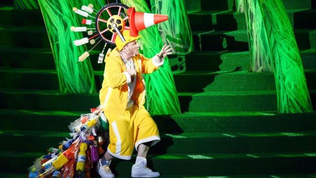 Mann in seltsamem Kostüm schleicht über eine Bühne.