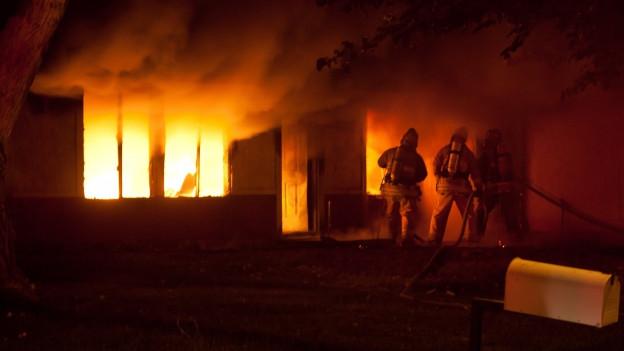 Feuerwehrmänner dringen in brennendes Haus ein