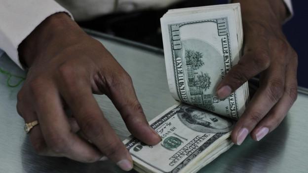 Eine Frau hälte Dollarnoten.