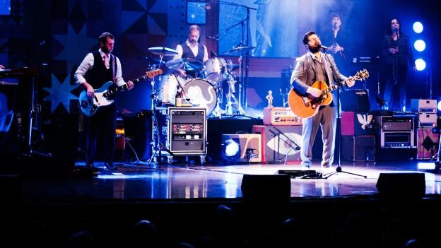 Band spielt auf einer Bühne. Verstärker stehen ihm Hintergrund.