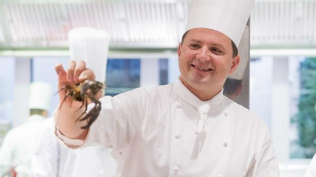 Ein Koch hält einen Krebs in der Hand.