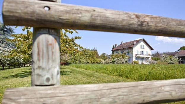 Ein Haus, durch einen Gartenzeaun hindurchfotografiert.