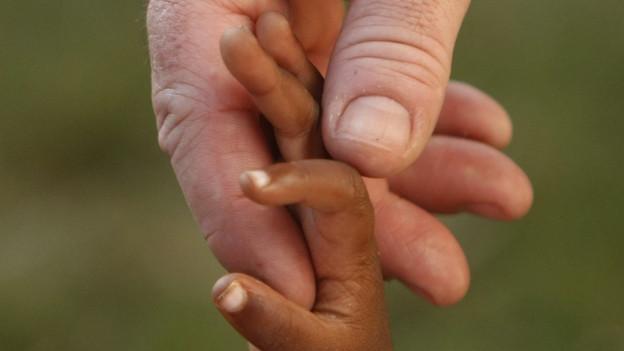 Eine grosse Männerhand hält eine Babyhand.