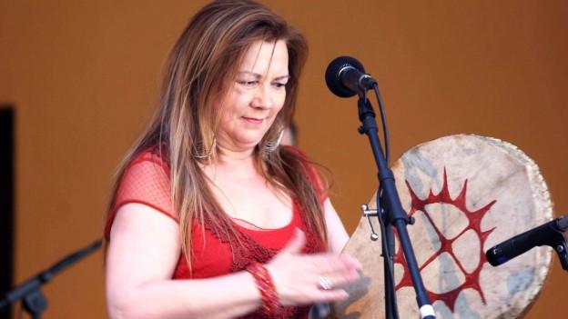 Frau vor Mikrofon schlägt auf Rahmentrommel.