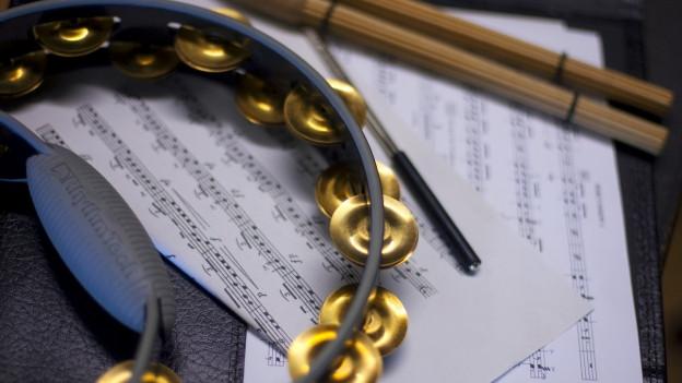 Ein Bild eines Schellenrings, Notenblätter und Schlagzeugstöcke.
