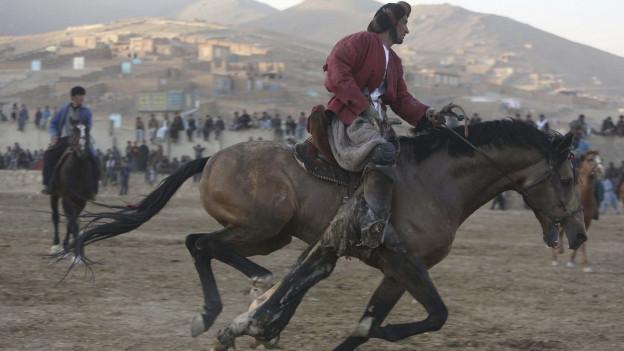 Ein Mann reitet ein Pferd.
