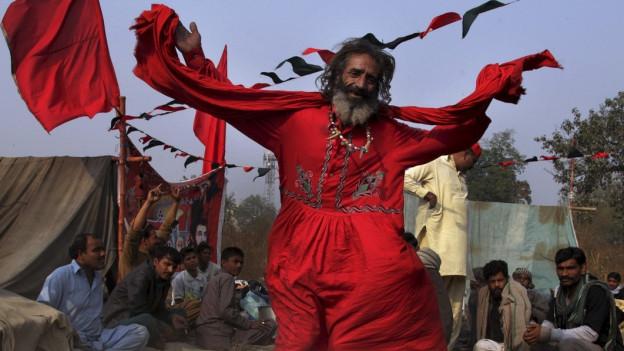 Ein älterer Mann tanzt in Lahore, Pakistan.